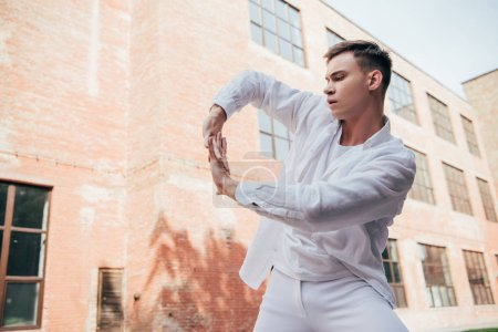 low angle view of young man in white clothes dancing on city street
