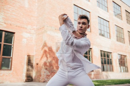 Photo for Young man in white clothes dancing on city street - Royalty Free Image