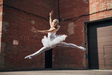 Photo for Beautiful young ballerina jumping and dancing on urban street - Royalty Free Image