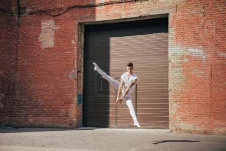 young ballet dancer dancing in jump on urban street