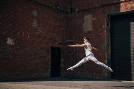 young ballet dancer in jump on city street