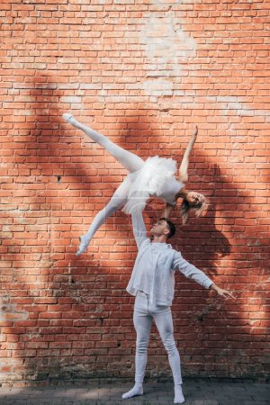 young couple of dancers performing ballet dance near brick wall