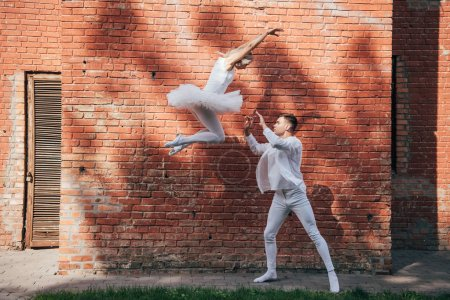 side view of beautiful young couple of dancers performing ballet dance on city street