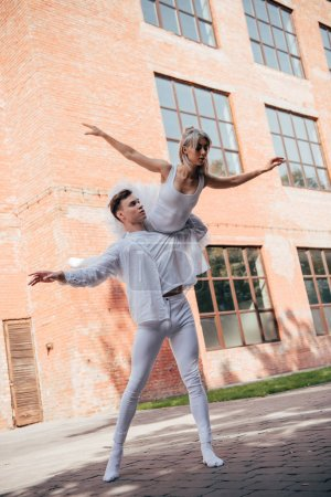 Photo for Low angle view of young ballet dancers in white clothes dancing on street - Royalty Free Image
