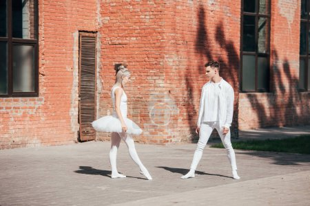 young ballet dancers in white clothes dancing on urban street