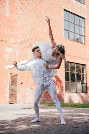 young ballet dancers in white clothes dancing on city street