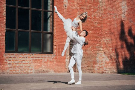 beautiful young couple of ballet dancers performing on urban city street