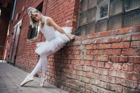 beautiful young ballerina leaning at brick wall and looking away
