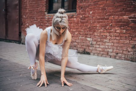 attractive young ballerina stretching on street