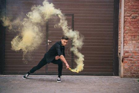 Foto de Joven bailando en amarillo humo en calle de la ciudad - Imagen libre de derechos