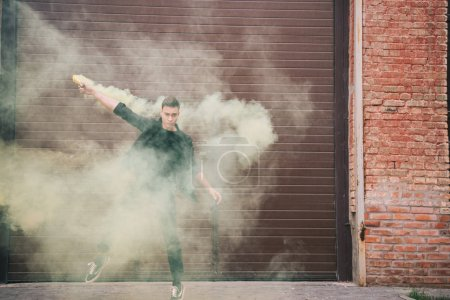 handsome male contemporary dancer in yellow smoke on urban city street