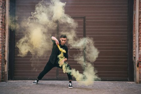 young male contemporary dancer in yellow smoke on urban city street