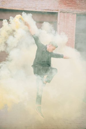 young male contemporary dancer jumping in smoke on urban street
