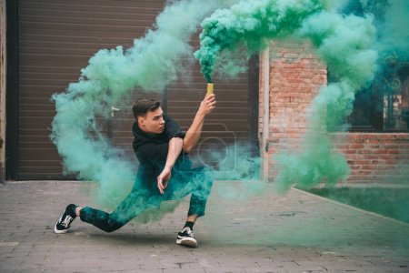 handsome young man dancing in green smoke on urban city street