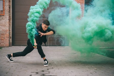 Photo for Young man dancing in green smoke on urban city street - Royalty Free Image