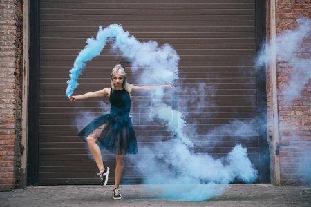 Foto de Chica bailando en humo azul y mirando a cámara en calle urbano de la ciudad - Imagen libre de derechos