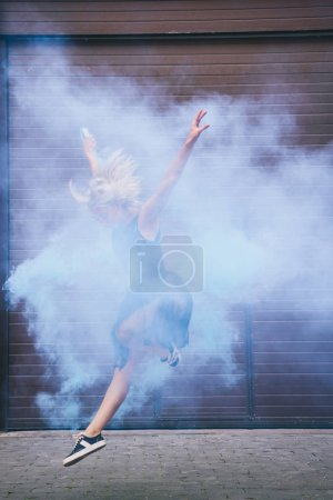 Photo for Young contemporary dancer dancing in blue smoke on street - Royalty Free Image