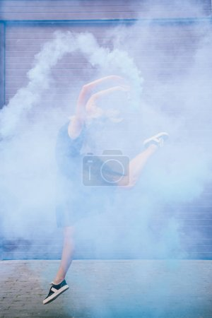 young female contemporary dancer dancing in blue smoke on street