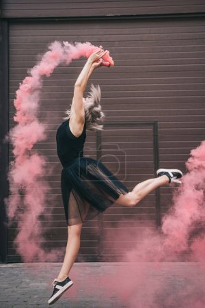 Photo pour Vue latérale d'une jeune danseuse danse en fumée rose sur la rue - image libre de droit