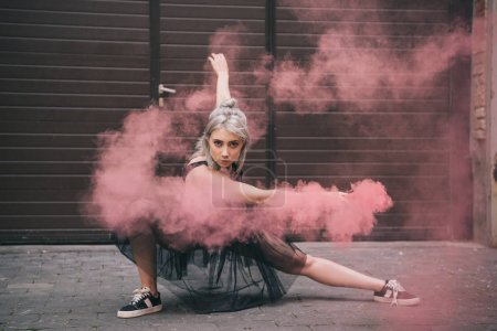 Photo for Beautiful girl dancing in pink smoke and looking at camera on street - Royalty Free Image