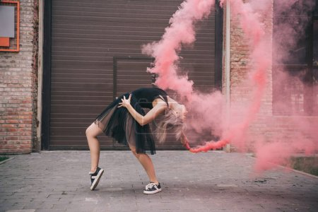 flexible girl dancing in pink smoke on urban street