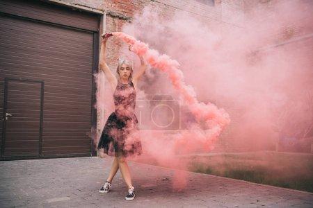young woman dancing in pink smoke on urban street
