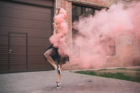 Photo for Young female contemporary dancer in pink smoke on street - Royalty Free Image