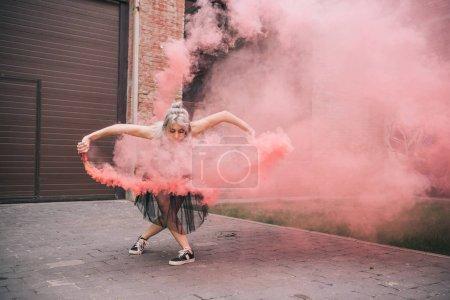 Photo pour Séduisante jeune danseuse danse en fumée rose sur la rue - image libre de droit