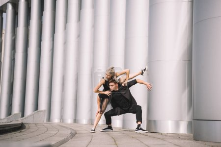beautiful young performers in black clothes dancing near columns on street