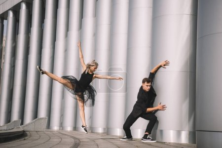 Photo for Beautiful young dancers in black clothes dancing near columns - Royalty Free Image