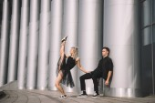 beautiful young couple in black clothes dancing near columns