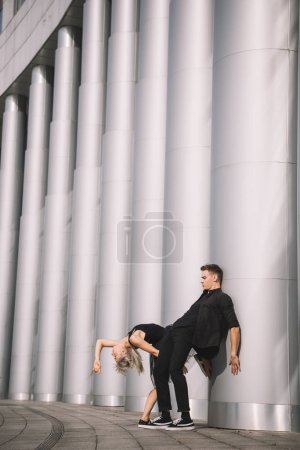 young couple in black clothes dancing near columns