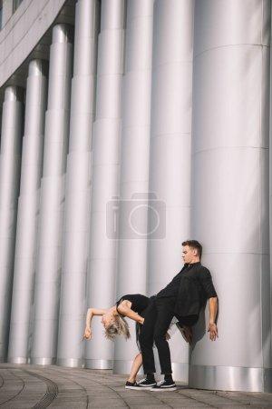 Photo pour Jeune couple en vêtements noirs dansant près de colonnes - image libre de droit