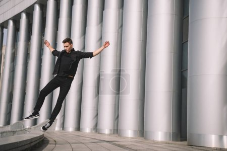 handsome young man in black clothes jumping in dance on street
