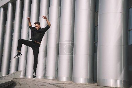 Foto de Atractivo joven en ropa negra bailando y saltando cerca de columnas - Imagen libre de derechos