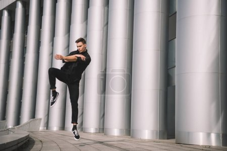 handsome young man in black clothes dancing near columns