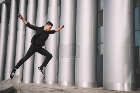 young male contemporary dancer in black clothes jumping on street