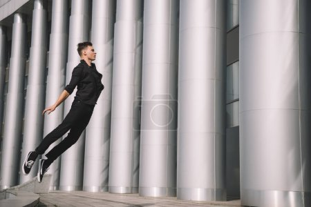 Photo for Young male dancer in black clothes jumping on street - Royalty Free Image