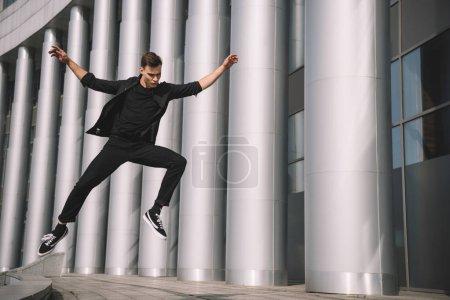 Foto de Atractivo joven en ropa negra saltando y bailando en la calle - Imagen libre de derechos