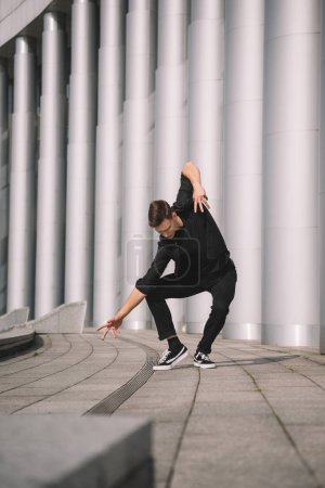 young contemporary dancer in black clothes on street