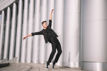 Photo for Handsome young modern dancer dancing near columns - Royalty Free Image