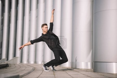young man performing contemporary dance on street