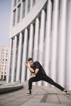 Photo for Handsome young man looking at camera while dancing on street - Royalty Free Image
