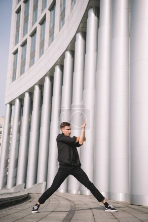 Photo for Young male dancer in black clothes near columns on street - Royalty Free Image