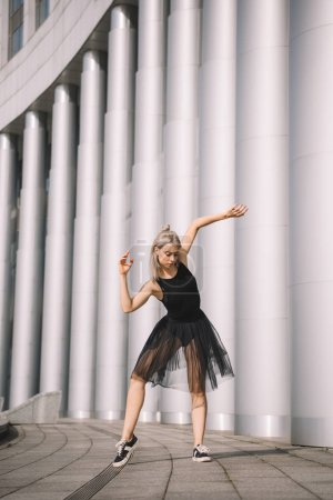 beautiful young woman in black skirt dancing near columns