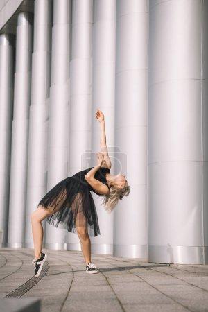 beautiful girl in black skirt dancing near columns on street