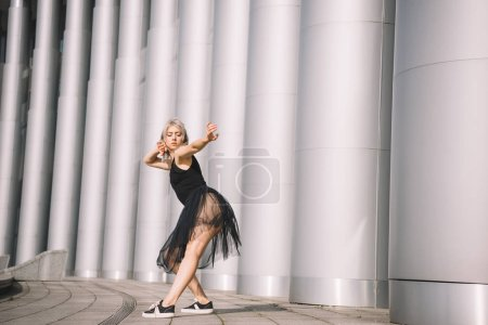 Photo for Side view of beautiful young dancer in black skirt near columns on street - Royalty Free Image
