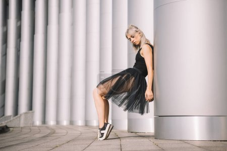 Photo for Side view of beautiful young female dancer leaning at column - Royalty Free Image