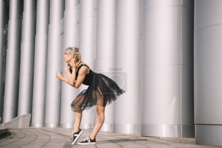 side view of attractive girl in black skirt dancing near columns