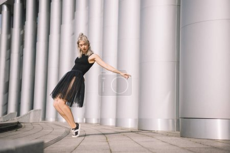 Photo for Beautiful young woman in black skirt dancing near columns - Royalty Free Image